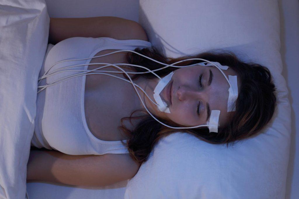 Junge Frau schlafend beim Messen der Gehirnströme